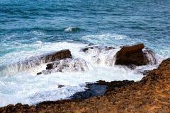 Sea waves crashing against the rocks . Stock Images
