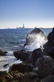 Sea waves crashing against the rocks. Mediterranean sea waves crashing against the coast rocks cliff, Barcelona on the horizon, Spain Stock Images
