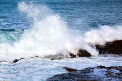Sea waves crashing against the rocks Stock Images
