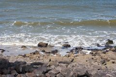 Sea waves crashing against stones lying by the shore royalty free stock photo