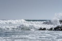 Sea waves crashing on beach rocks with simple horizon and clear sky. Splashing waves on beach. Royalty Free Stock Images
