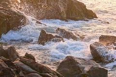 Sea waves crashing on coastal rocks in the rays royalty free stock image