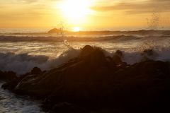 Sea waves crashing onto the rocks on sunset royalty free stock image