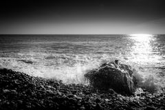 Sea waves crashing on a rock in the beach. Black and white. Stock Image