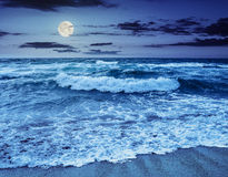 Sea ​​waves crashing on sandy beach at night Royalty Free Stock Image
