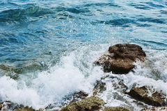Sea waves crashing with splash by the stone rocks in windy day. Sea waves crashing with splash by the stone rocks in windy day Stock Image