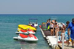 Sea waves in Cyprus Mediterranean sea, water motorcycles. Sea waves in Cyprus Mediterranean sea, blue and clear water, view from the beach, water motorcycles Stock Image