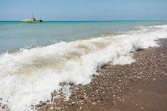 Sea waves with defocused motor boat Stock Photos
