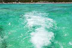 Sea waves from a fast speed boat on the blue aqua water with tropical island background. Stock Photo