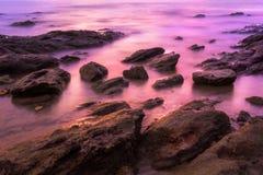 Sea waves flow on rock beach Stock Photos