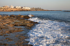 Sea waves with foam on the stony shore. Mediterranean town in th Stock Image