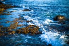 Sea waves with foam on the stony shore. Toned Stock Photos