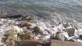 Sea waves and foams on stones. stock video footage