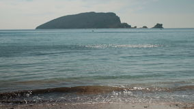 By the sea waves gently pleshutsya against the black mountain. stock video