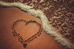 Sea waves and heart drawing on the sand beach near the ocean. Summer love concept. Sea waves and heart drawing on the sand beach near the ocean. Summer love stock photo
