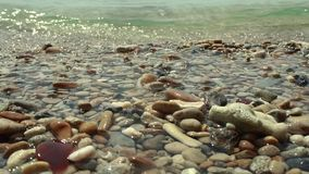The sea waves hit the beach full of gravel. stock video footage