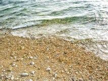 Sea waves hitting a colorful pebble beach royalty free stock image