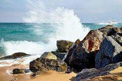Sea waves hitting the rocky beach at Malgrat de Mar, Spain. Salty sea water, waves, sun, sand, rocks and holidays summer and heat Stock Photography