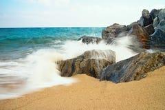 Sea waves hitting the rocky beach at Malgrat de Mar, Spain. Salty sea water, waves, sun, sand, rocks and holidays. Summer and heat. Sea waves hitting the rocky Stock Photo