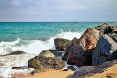 Sea waves hitting the rocky beach at Malgrat de Mar, Spain. Salty sea water, waves, sun, sand, rocks and holidays. Summer and heat. Sea waves hitting the rocky Stock Photography
