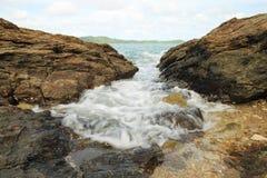 Sea waves hitting round rocks Stock Image