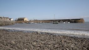 Sea and waves lapping on pebbles Minehead harbour Somerset England with boats in summer stock footage