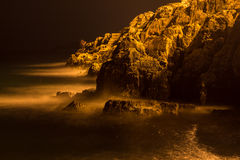 Sea waves lash line impact rock on the beach in night Royalty Free Stock Image