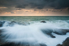 Sea waves lash line impact rock on the beach Stock Images