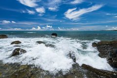 Sea waves lash line impact rock on the beach under blue sky Stock Images