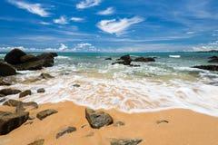 Sea waves lash line impact rock on the beach under blue sky Royalty Free Stock Photos