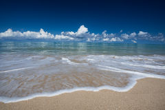 Sea waves lash line impact on the sand beach under blue sky Stock Image