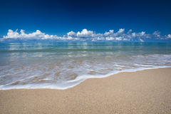 Sea waves lash line impact on the sand beach under blue sky Royalty Free Stock Images