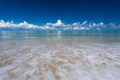 Sea waves lash line impact on the sand beach under blue sky Royalty Free Stock Photos