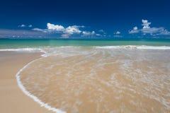 Sea waves lash line impact on the sand beach under blue sky Stock Photos