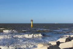 The sea with waves and a lighthouse in cadzand in holland in winter and a blue sky. Waves in the sea and a lighthouse in cadzand, zeeland, holland and a blue sky royalty free stock photography