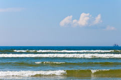 Sea and waves and  lonely ship over blue sky Royalty Free Stock Image