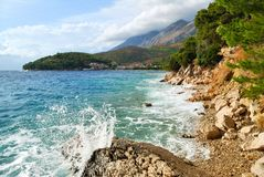 Sea Waves and Mountains in Clouds Stock Photo
