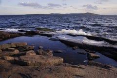 Sea waves pour stony shore islands. Sea waves pour stony shore cliffs in the background Island Royalty Free Stock Photography