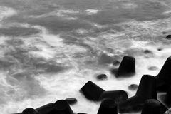 Sea waves pouring over tetrapod breakwater Royalty Free Stock Images