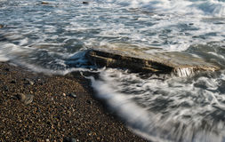 Sea waves and rock. Sea waves flowing above a sea rock creating a beautiful nature water background. Long exposure photo Stock Photo