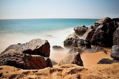 Sea waves and rocks on the beach in Malgrat de Mar, Spain. Salty sea water, waves, sun, sand, rocks and holidays summer and heat Stock Images