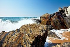Sea waves and rocks on the beach in Malgrat de Mar, Spain. Salty sea water, waves, sun, sand, rocks and holidays summer and heat Royalty Free Stock Photos