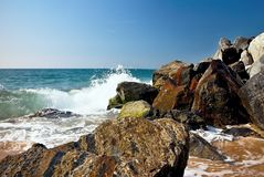 Sea waves and rocks on the beach in Malgrat de Mar, Spain. Salty sea water, waves, sun, sand, rocks and holidays summer and heat Royalty Free Stock Photo