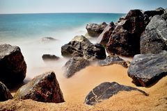 Sea waves and rocks on the beach in Malgrat de Mar, Spain. Salty sea water, waves, sun, sand, rocks and holidays summer and heat Stock Photo