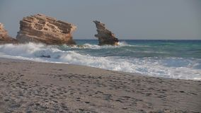 Sea waves on the rocky shoreline full HD. Slow motion shot of stormy sea waves crashing on the rocky shoreline at sunset. Famous triopetra beach, Crete, Greece stock footage
