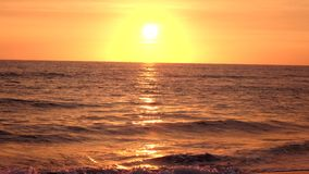Sea waves rolled on a sandy beach in the rays of the setting sun. Against the yellow orange horizon stock video