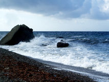 Sea waves rolling on stones Stock Photos
