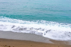 Sea, waves, sand. Brown sand, waves, turquoise sea. The Black Sea, Sudak Bay, Crimea stock image
