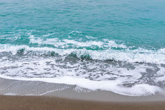 Sea, waves, sand. Brown sand, waves, turquoise sea. The Black Sea, Sudak Bay, Crimea royalty free stock image