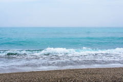 Sea, waves, sand. Brown sand, waves, turquoise sea. The Black Sea, Sudak Bay, Crimea stock photo